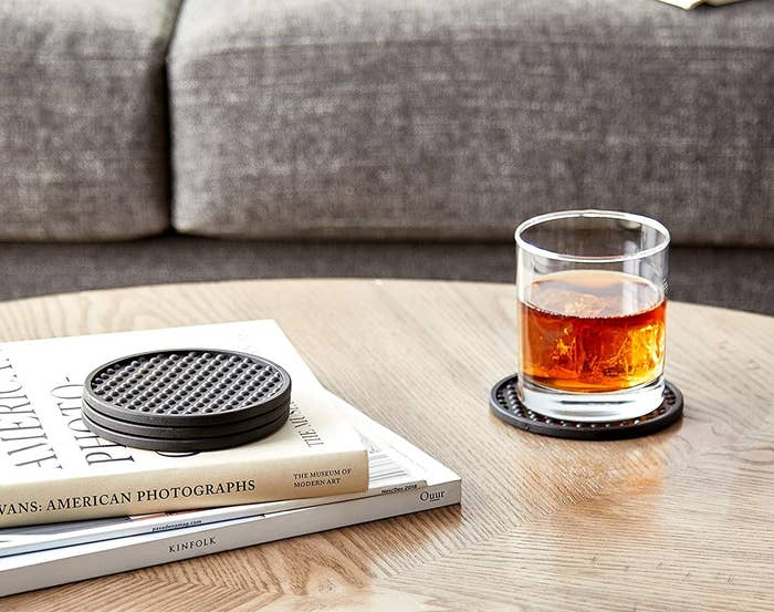 A glass of brown liquor on one of the bubble coasters on a wooden coffee table