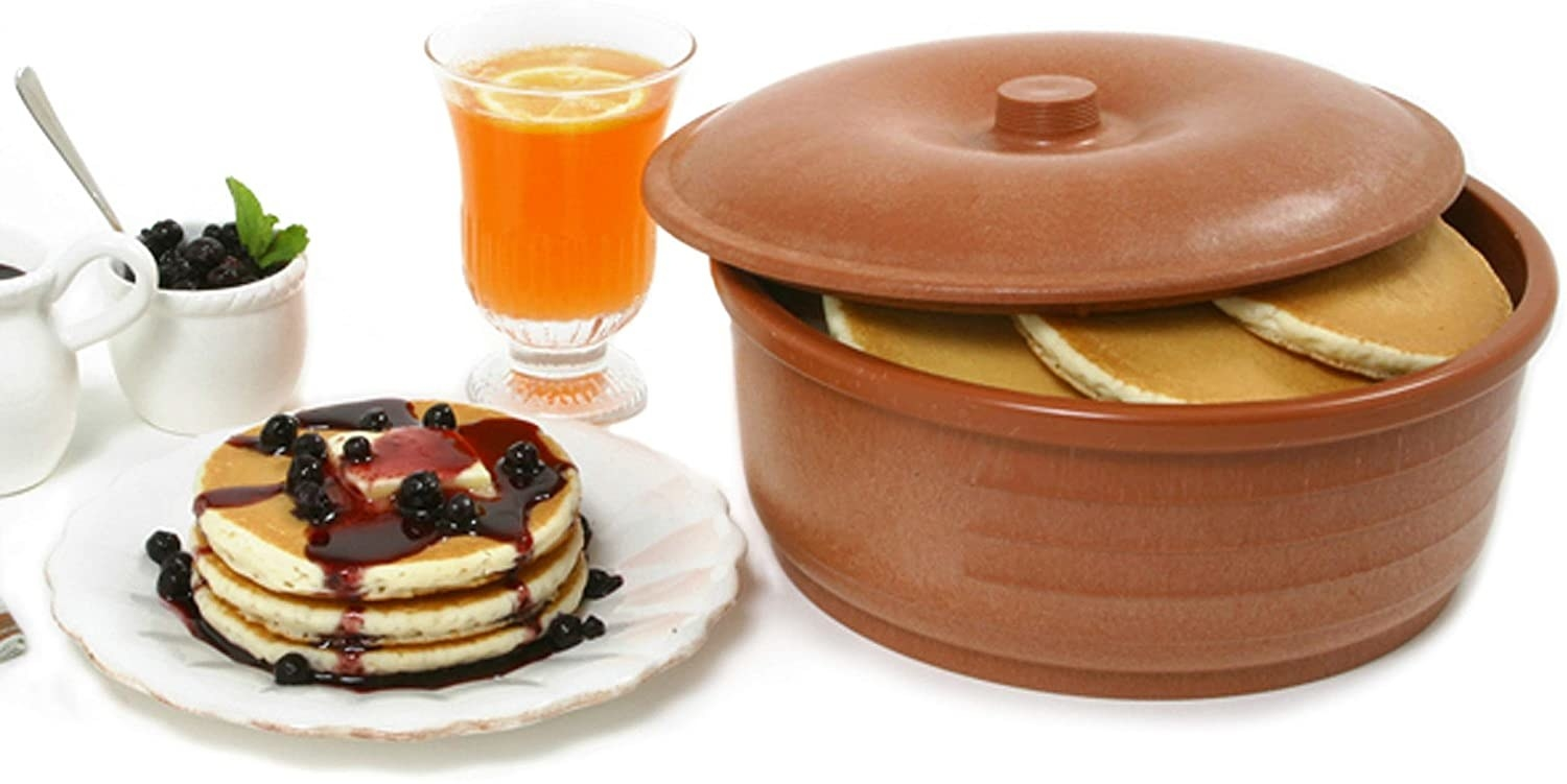 A close up of the keeper stuffed with pancakes, next to a plate of neatly stacked flapjacks