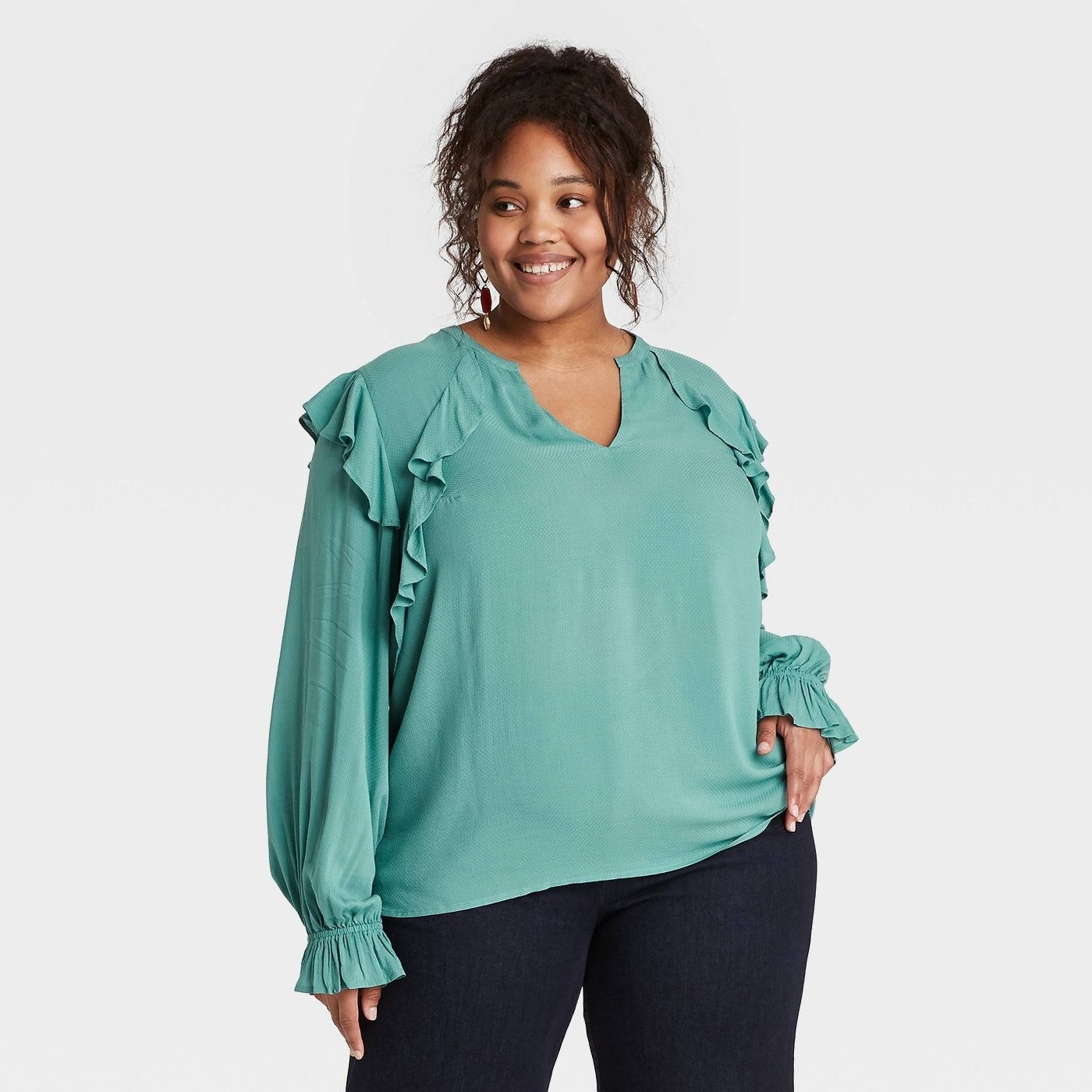 Model wearing teal blouse