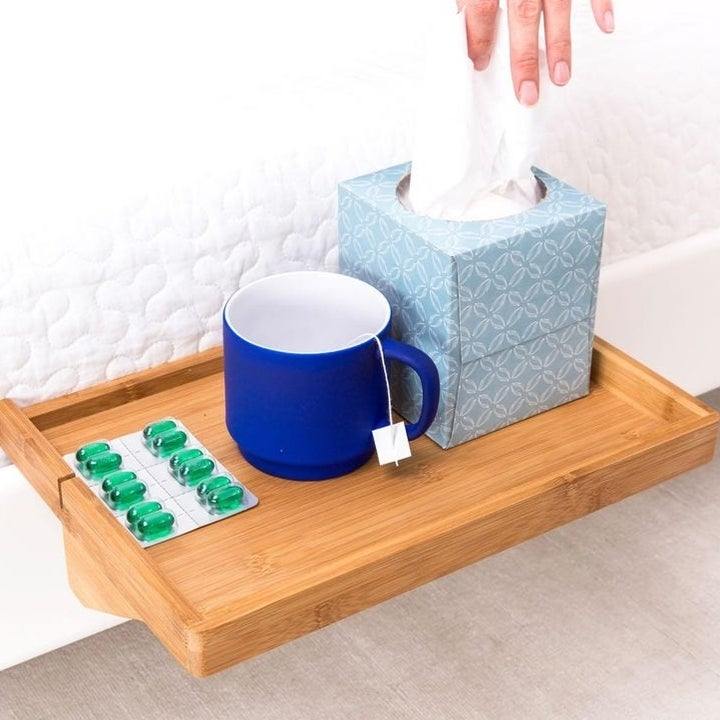 closeup of the table, showing it holding a tissue box, mug and medicine