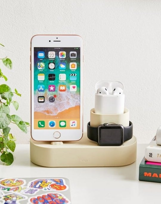 An iPhone sits on one side of the cylindrical charging hub, with an Apple watch around a cup-shaped portion of the hub that holds AirPods