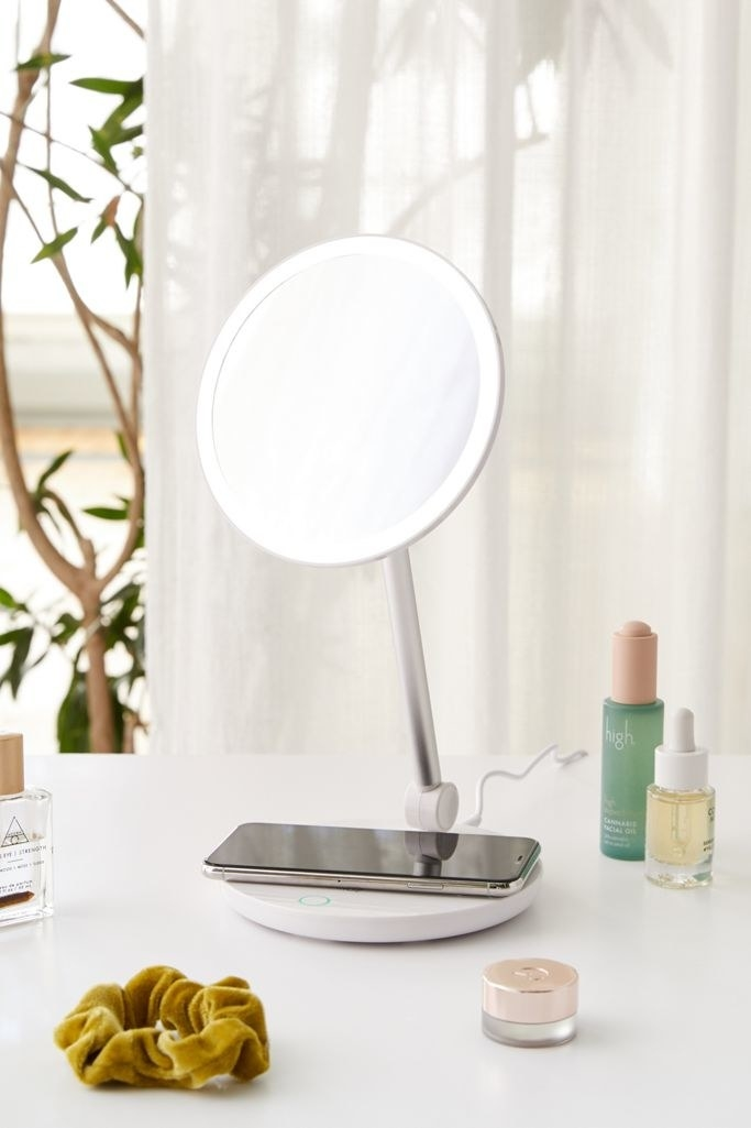A round vanity mirror with lit up edges and a round base that doubles as a wireless charger