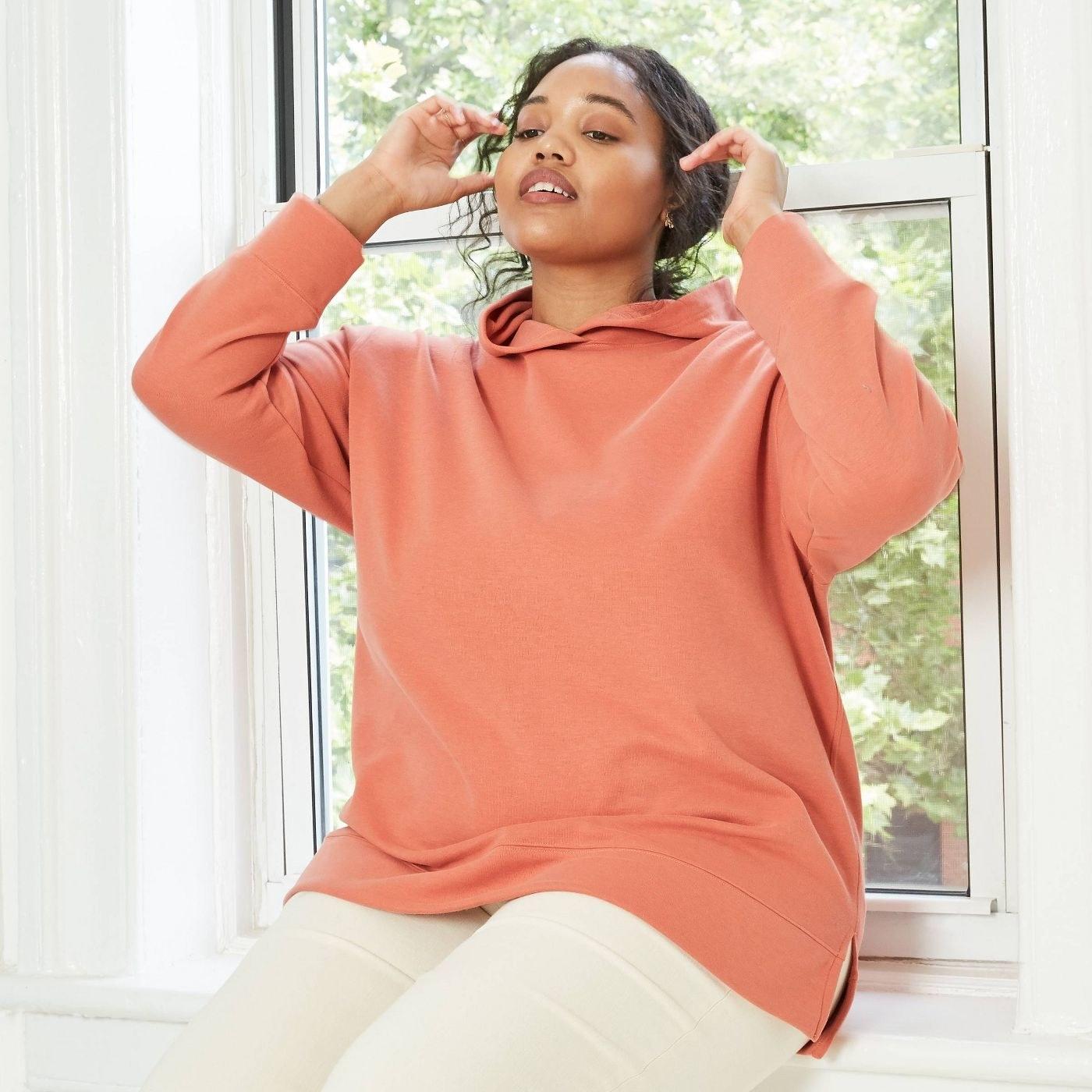 Model wearing orange hoodie