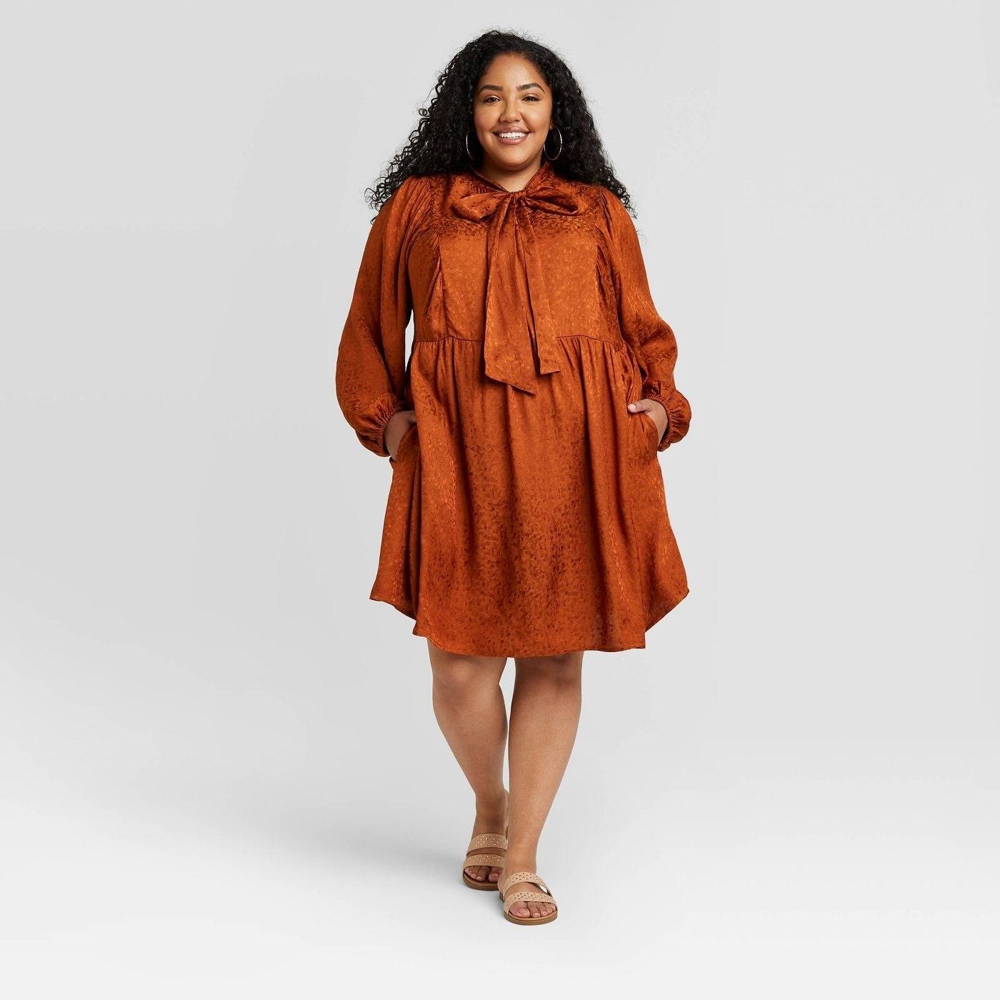 Model wearing rust dress