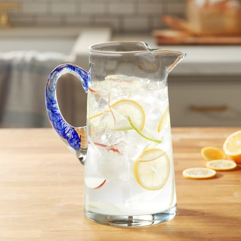 The glass pitcher with blue handle