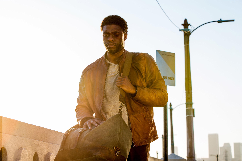 Chadwick Boseman with a black eye carrying a duffel bag