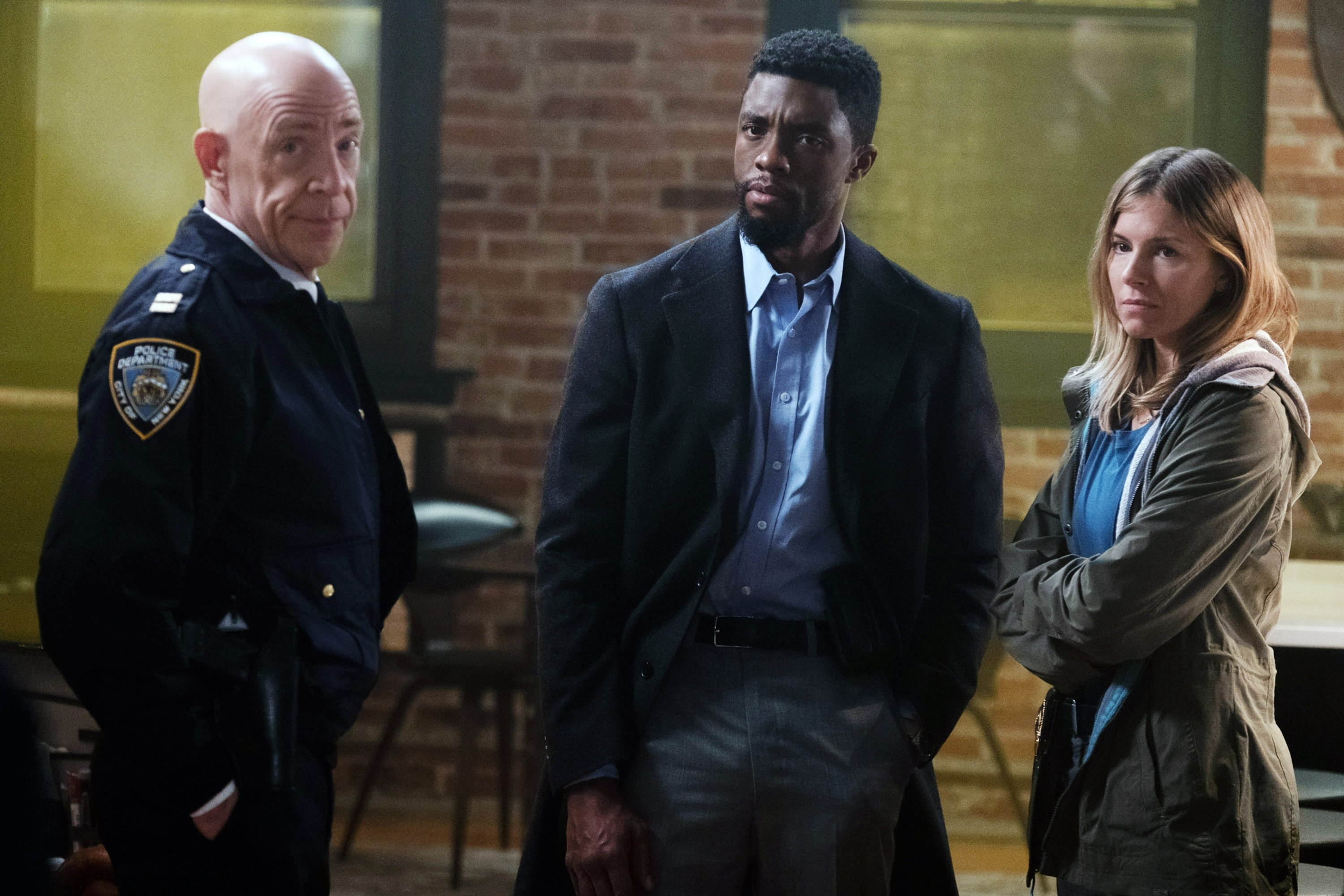 Chadwick Boseman as a detective standing between J.K. Simmons and Sienna Miller