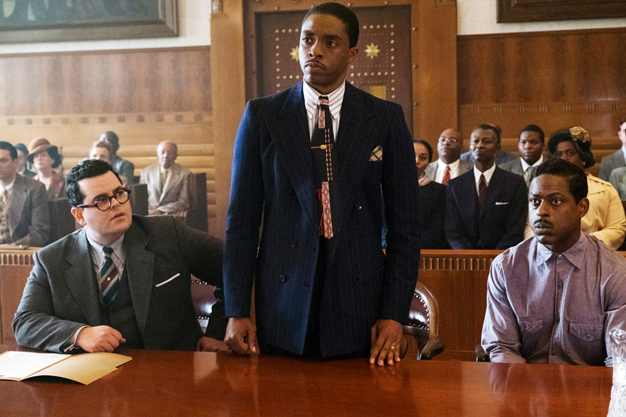 Chadwick Boseman as Thurgood Marshall standing in a courtroom between Josh Gad and Sterling K. Brown