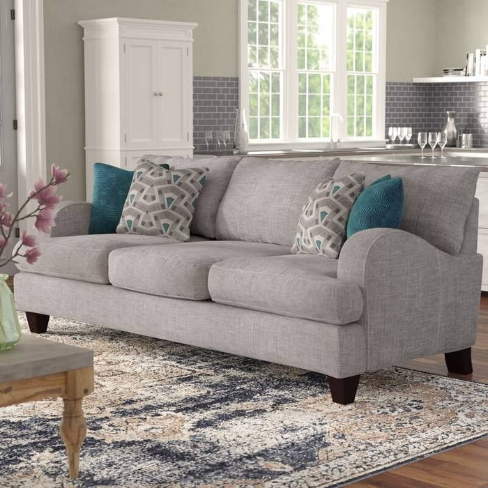 The gray fabric sofa with its teal and gray patterned throw pillows