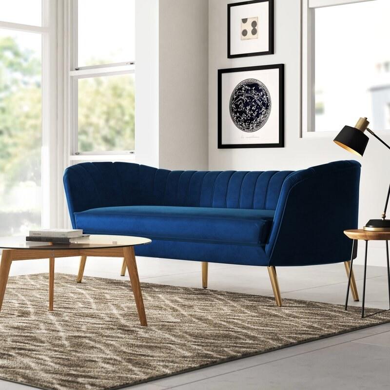 The navy blue velvet sofa with gold legs