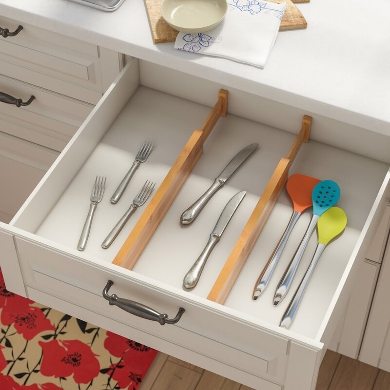 A pair of wooden, adjustable drawer dividers separating kitchen utensils and silverware