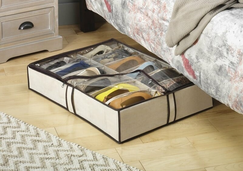 A white, under-bed shoe bag with a clear cover holding 12 pairs of shoes