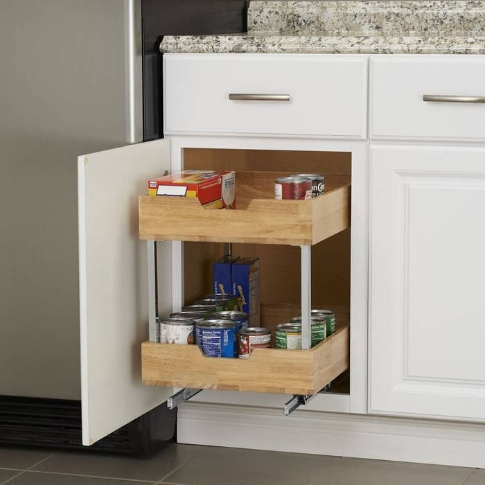A wood and metal two-tier pull-out drawer holding pantry staples in a kitchen cabinet