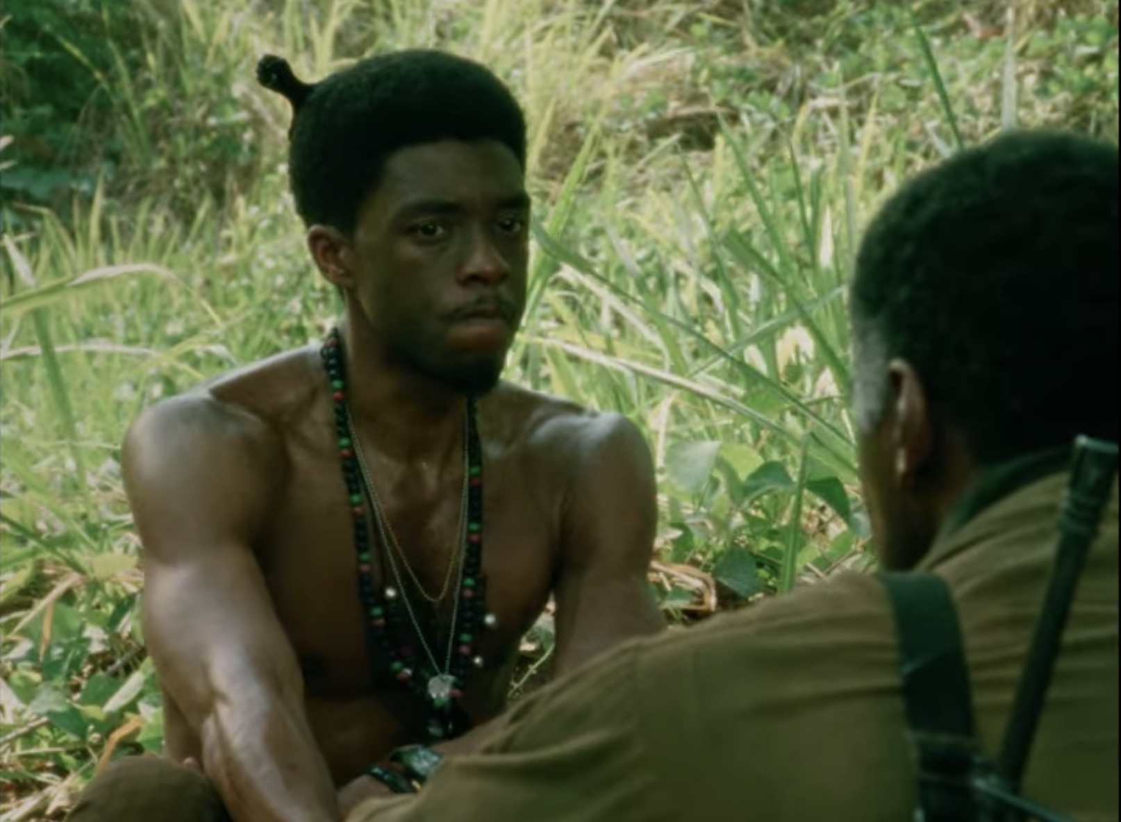 Chadwick shirtless with an afro pick in his hair sitting in the jungle