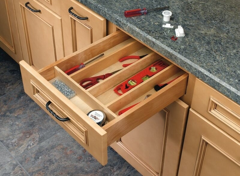 A wooden kitchen utensil organizer holding a variety of tools
