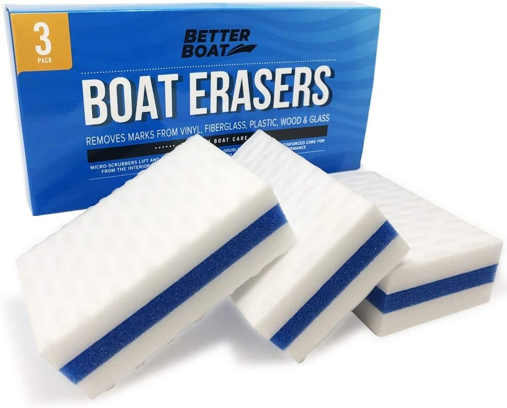 Three of the erasers in white with a blue stripe in the middle sitting in front of the box