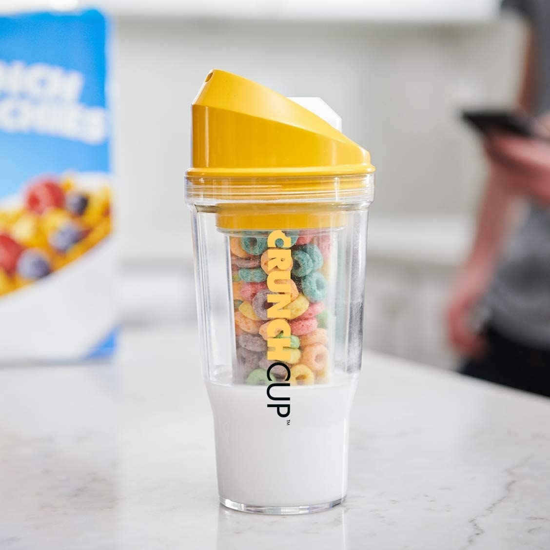 A cereal cup filled with milk and cereal on a kitchen counter