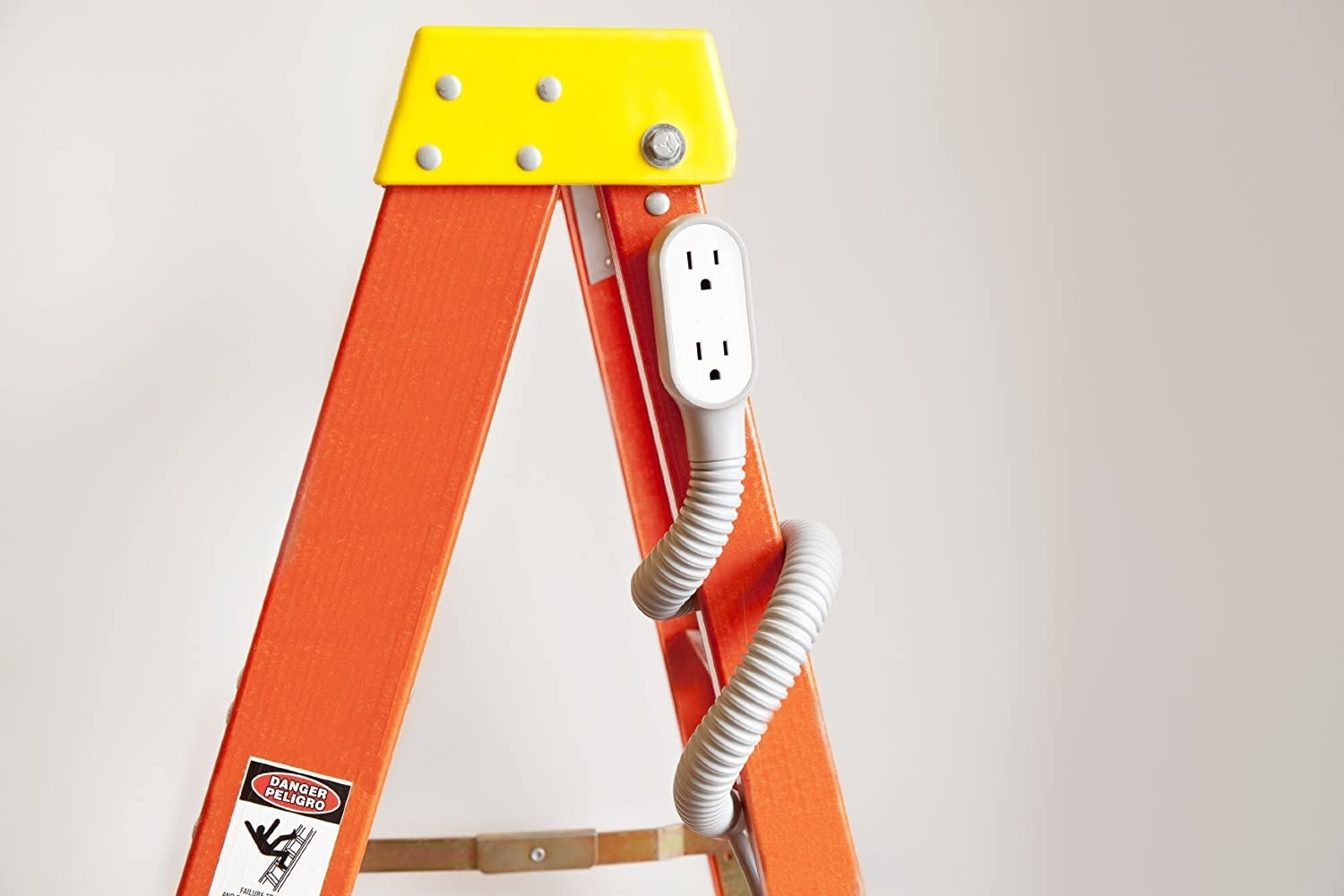 The extension cord wrapped around a ladder