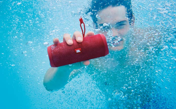 Model holding the cylinder-shaped speaker in red underwater