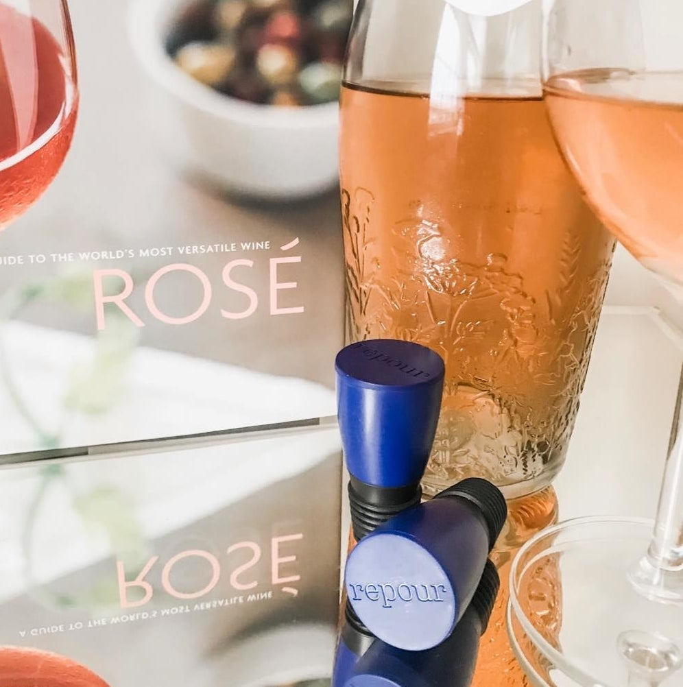 A pair of wine-saving corks next to a bottle of rosé