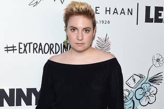 Lena Dunham poses at an event wearing black dress
