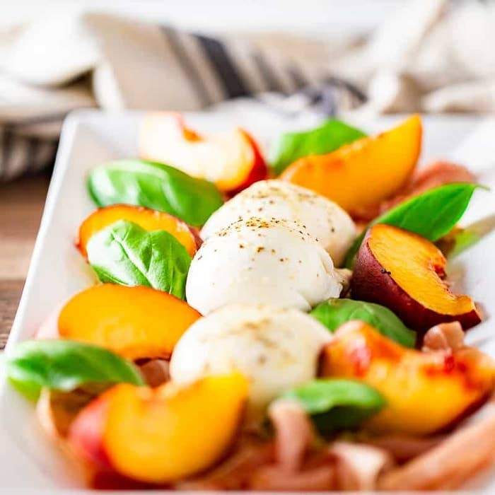 A plate with balls of burrata, sliced peaches, basil leaves, and prosciutto.
