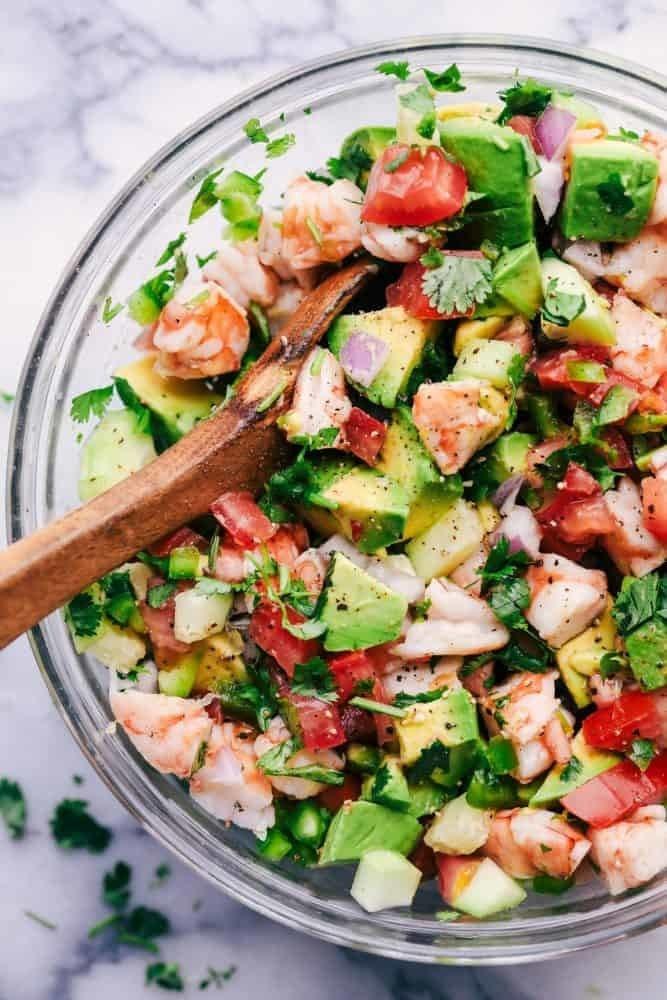 A bowl of shrimp, avocado, tomato, and cilantro marinated in lime.