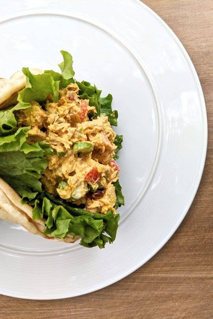 A pita filled with curried tuna salad and lettuce.