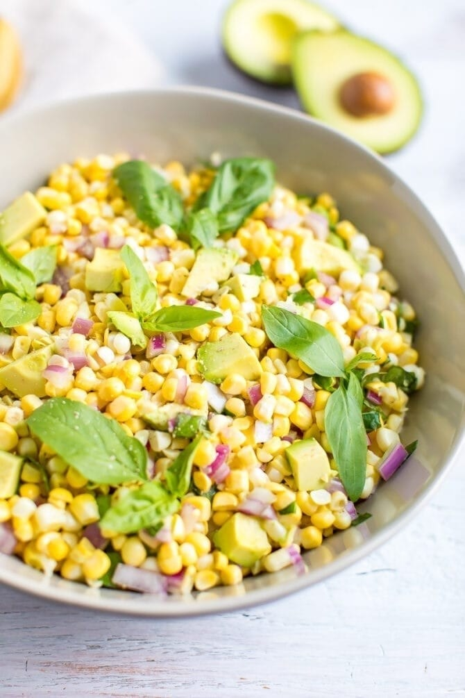 A bowl of raw corn salad with avocado, red onion, and basil leaves.