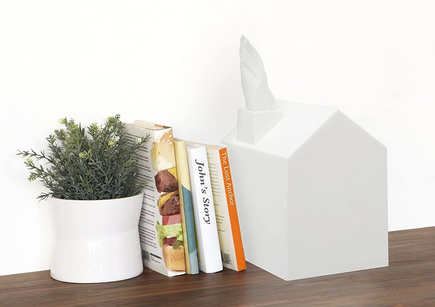 a white tissue box cover shaped like a house, the tissue looks like smoke coming out of the chimney
