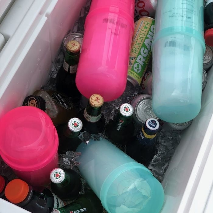 Two hot pink and two teal SubSafes in a cooler full of drinks, showing how they're waterproof