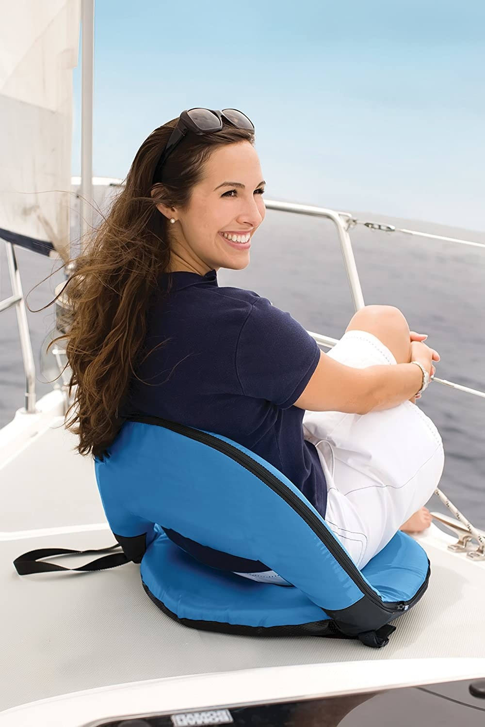 Model sitting on the blue recline seat on the front of a sailboat