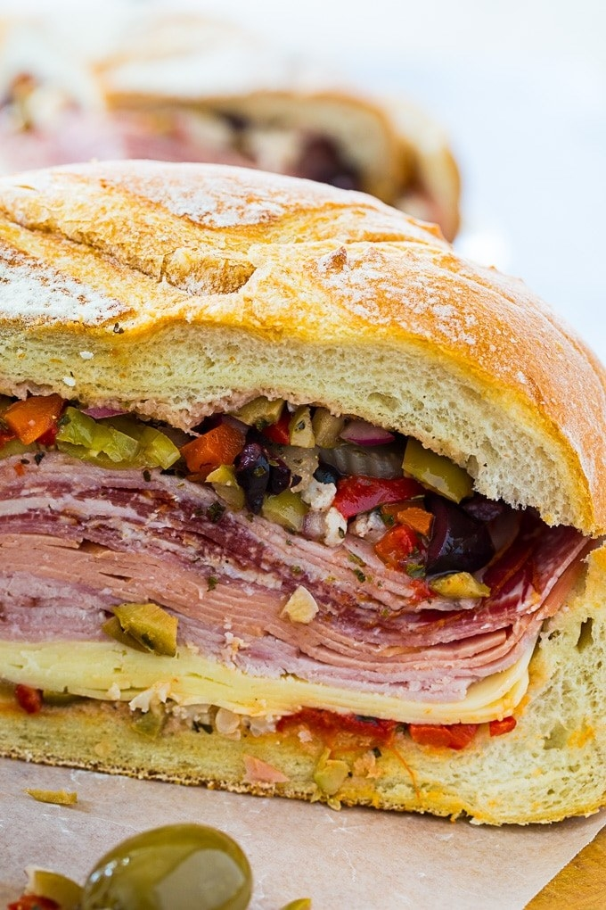 A roll filled with sliced cheese, salami, ham, and olive salad.
