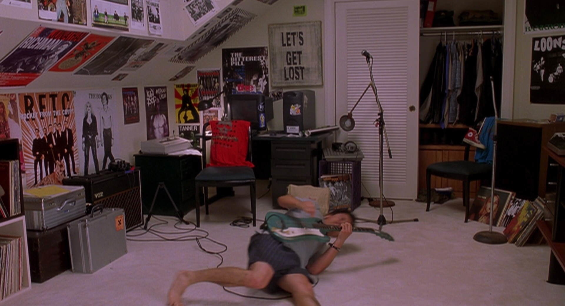 Cliff plays guitar on the floor.