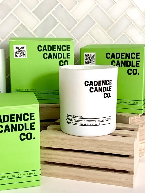 """a white glass candle with the words """"cadence candle co."""" on it and three lines that note the scent and the burn time"""