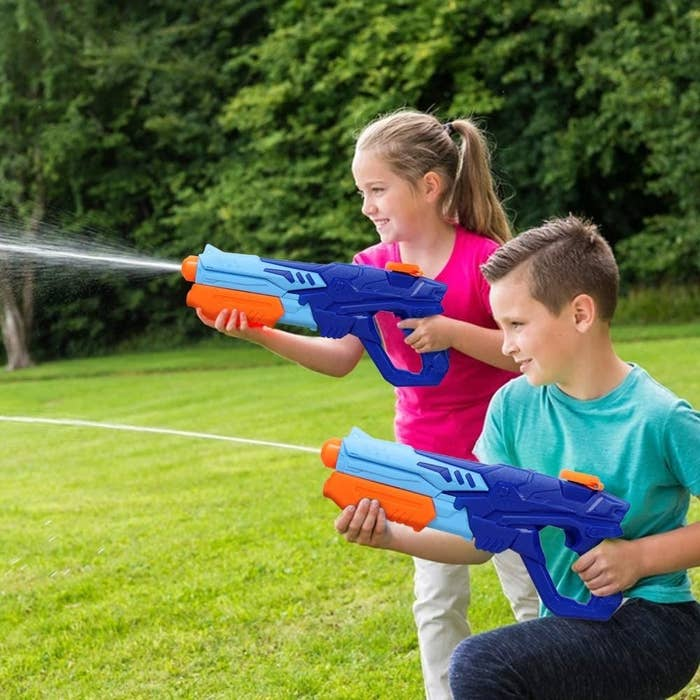 two kids spraying water from the water guns