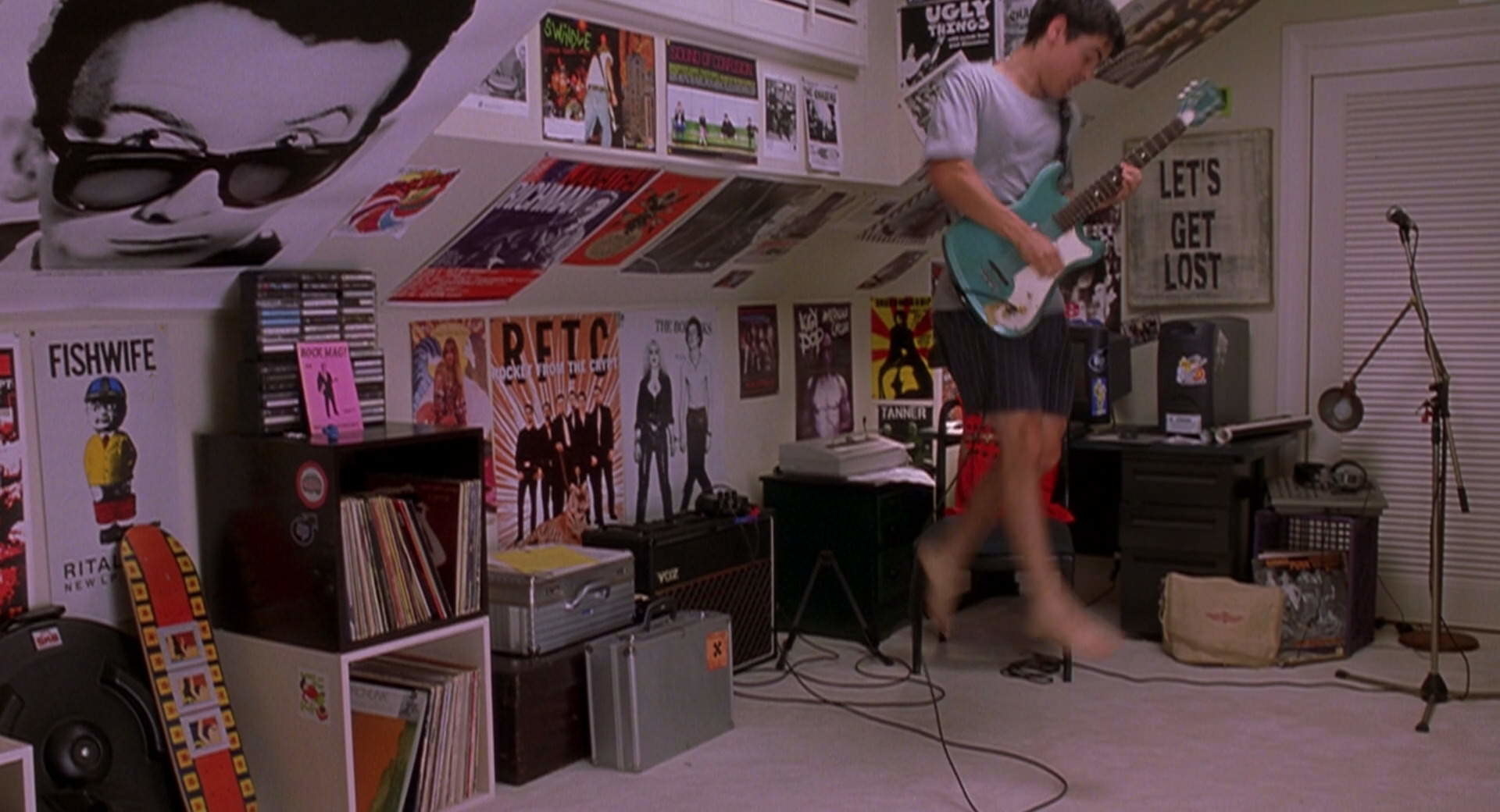 Cliff jumps around his room playing guitar.