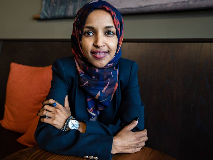 Ilhan Omar sits with arms crossed