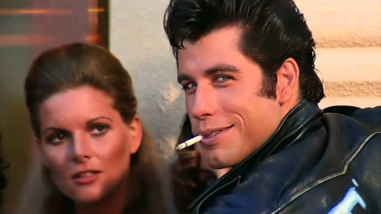 Danny Zuko looking at the T-Birds, leaning against the wall while smoking a cigarette