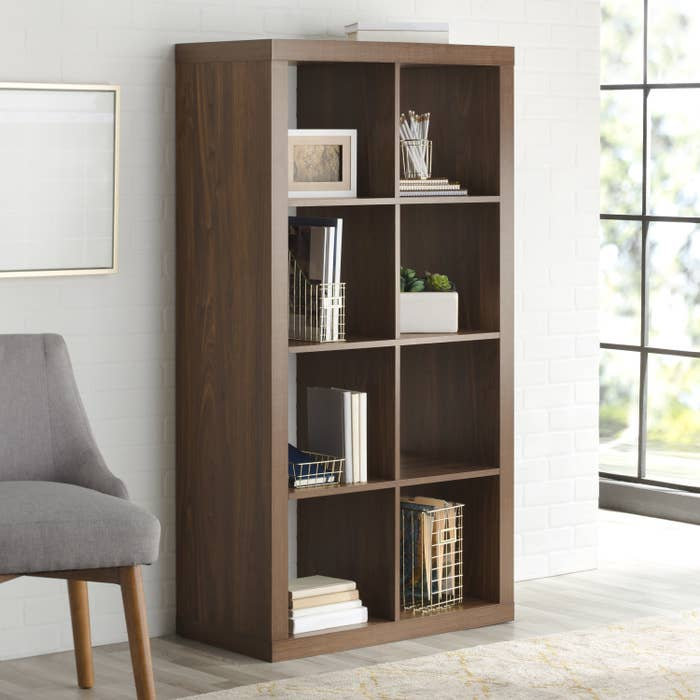 A tall shelving unit in brown with eight square sections