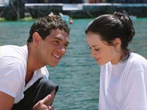 Kostas looking at Lena lovingly while they sit on the dock near the water in Greece