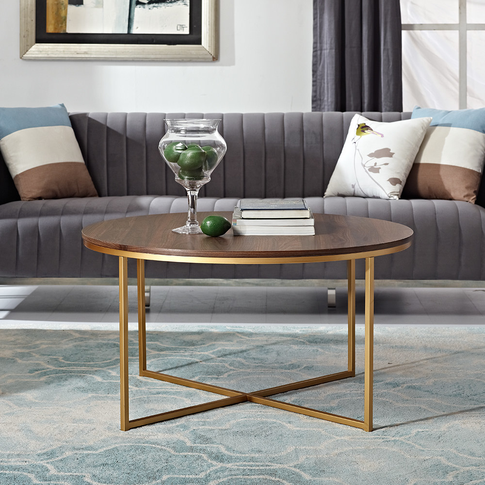 A round wooden coffee table with gold legs