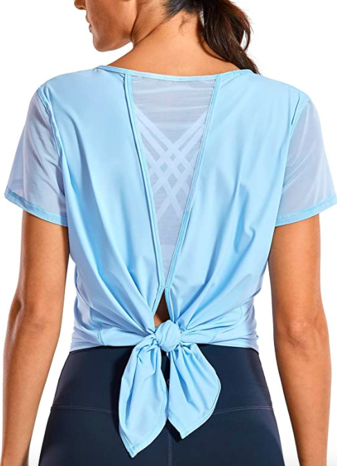 Model wears light blue tie-back short-sleeve top with navy blue workout leggings