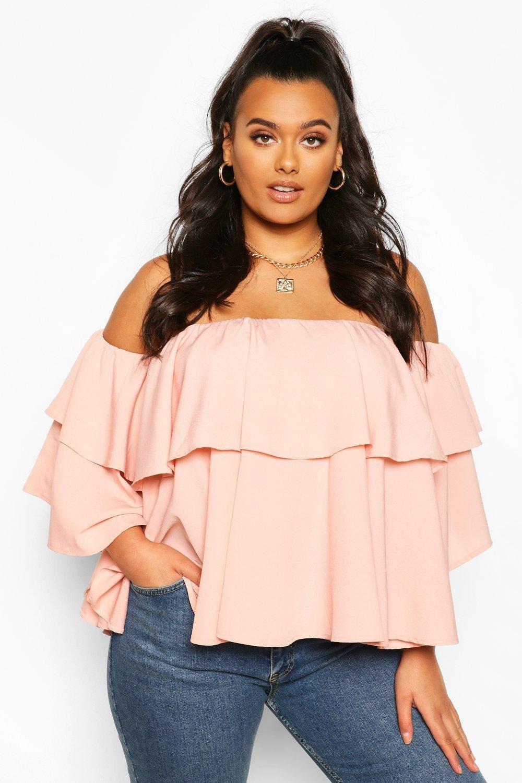 model wearing blush off-shoulder ruffled top