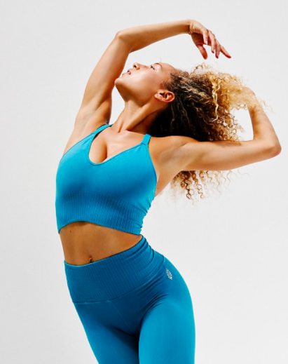 Model wears blue Free People workout crop top with matching blue leggings