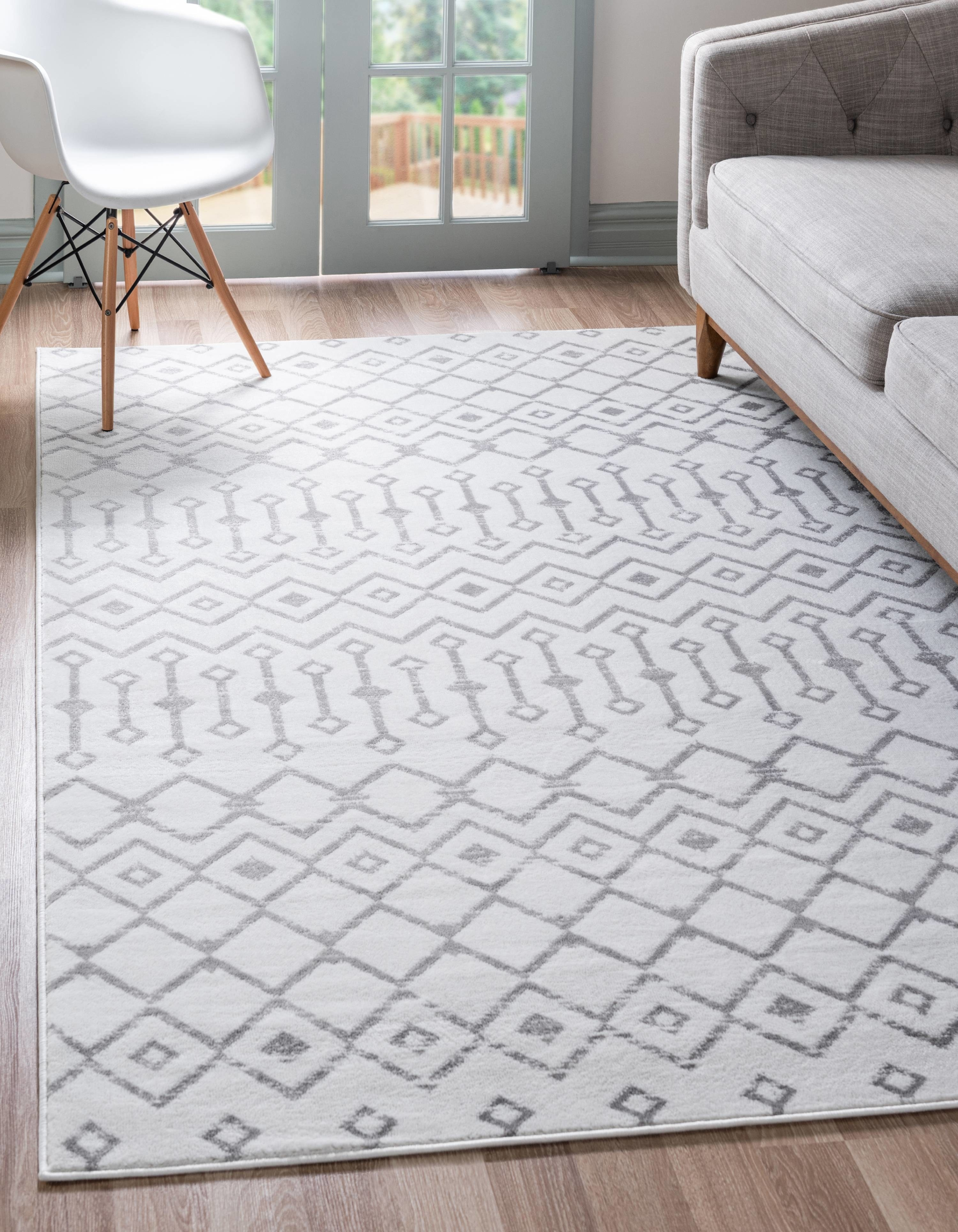 a white rug with a grey Moroccan design on it