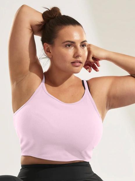 Model wears pink Athleta twist back cami with black leggings