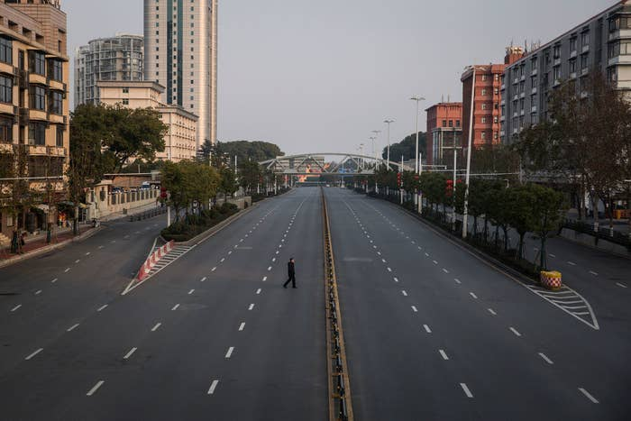 Lone person walking across an empty highway in Wuhan, China
