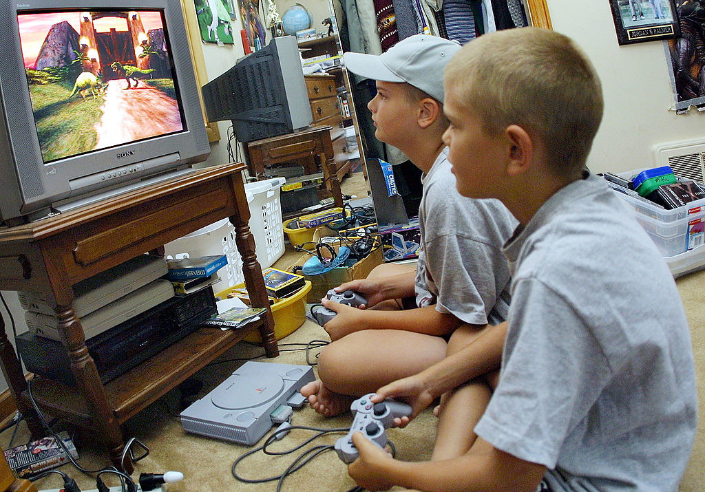Two young children playing a PlayStation video game in their parent''s home.