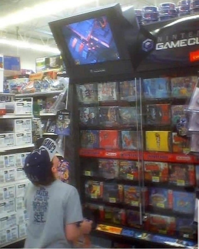 A photo of kid playing a Nintendo GameCube at a display in a store.